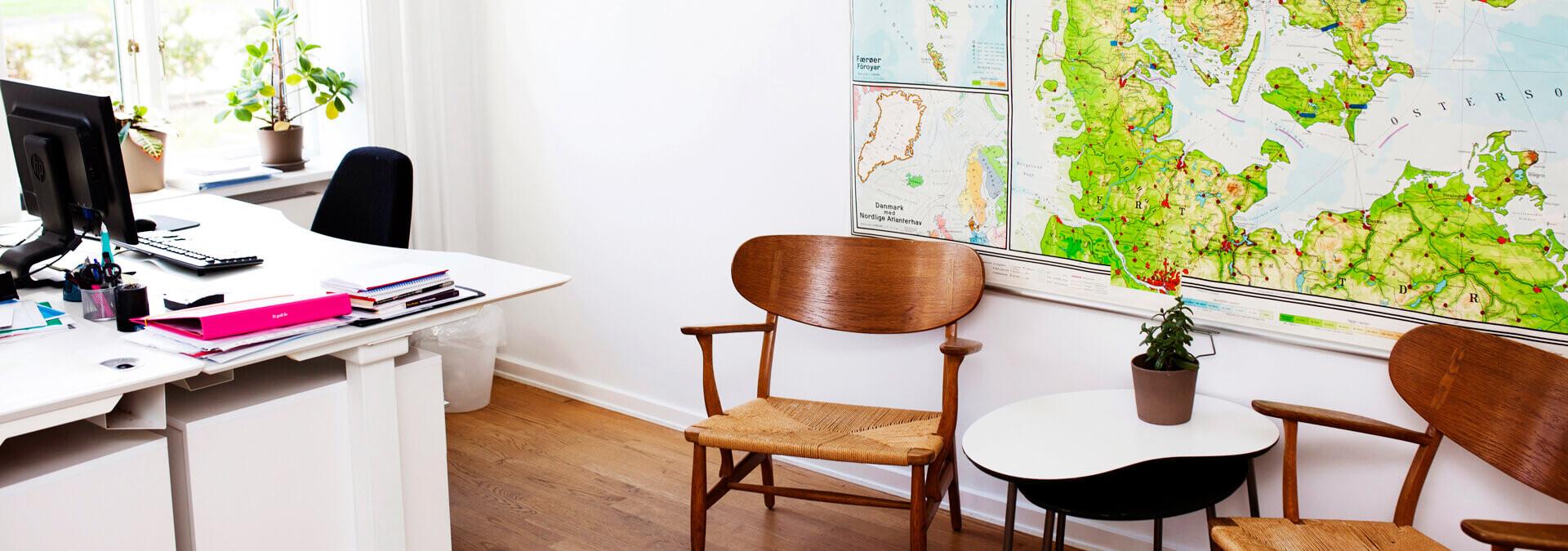 Kontor på krisecenter med skrivebord, stole og et landkort
