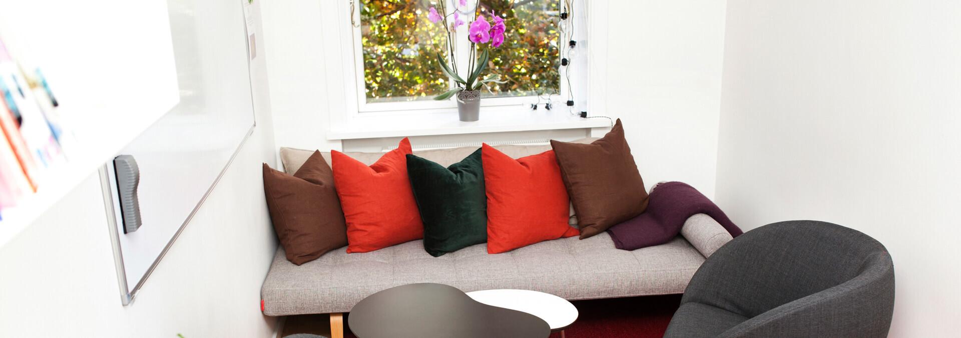 Sofa på krisecenter med puder og tæppe