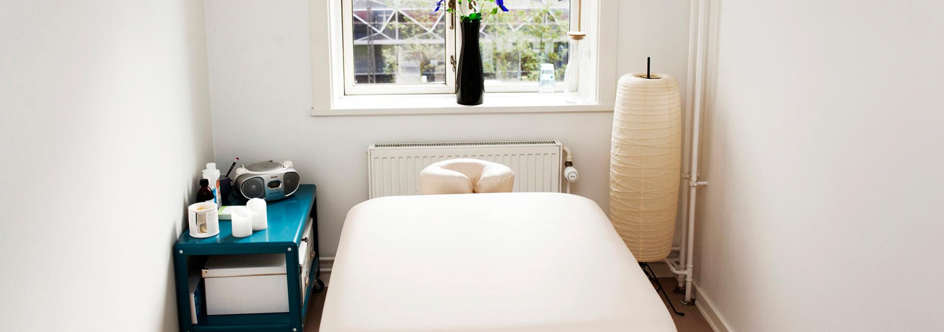 Hvid massagebriks med lys, musik og blomster på krisecenter
