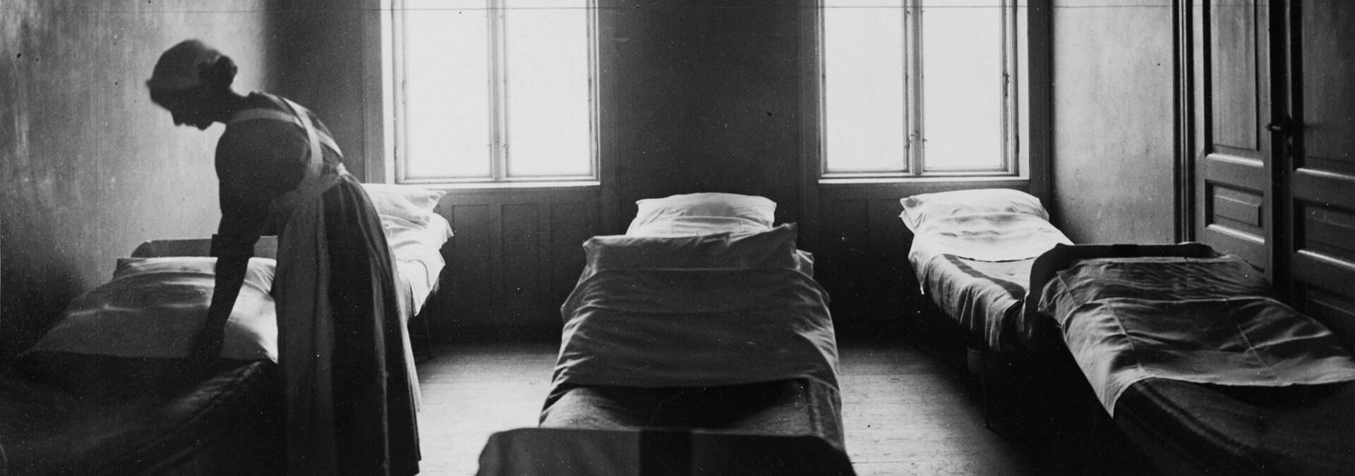 En kvinde reder en seng på en sovesal for kvinder og børn, Kvindehjemmets historie