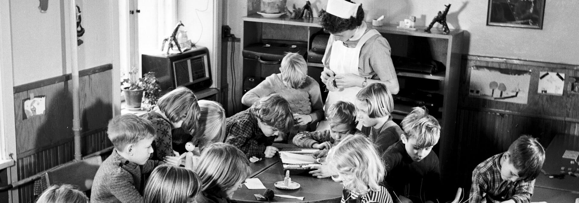 Børnene i børnehaven sidder rundt om et bord og fletter, Kvindehjemmets historie
