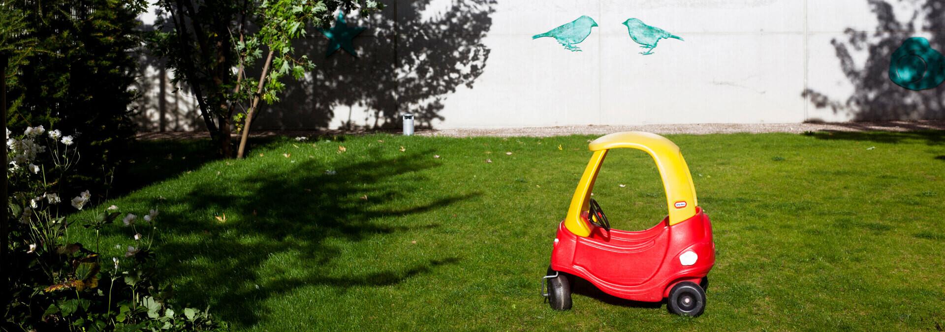Have på krisecenter med træer og gul og rød legebil