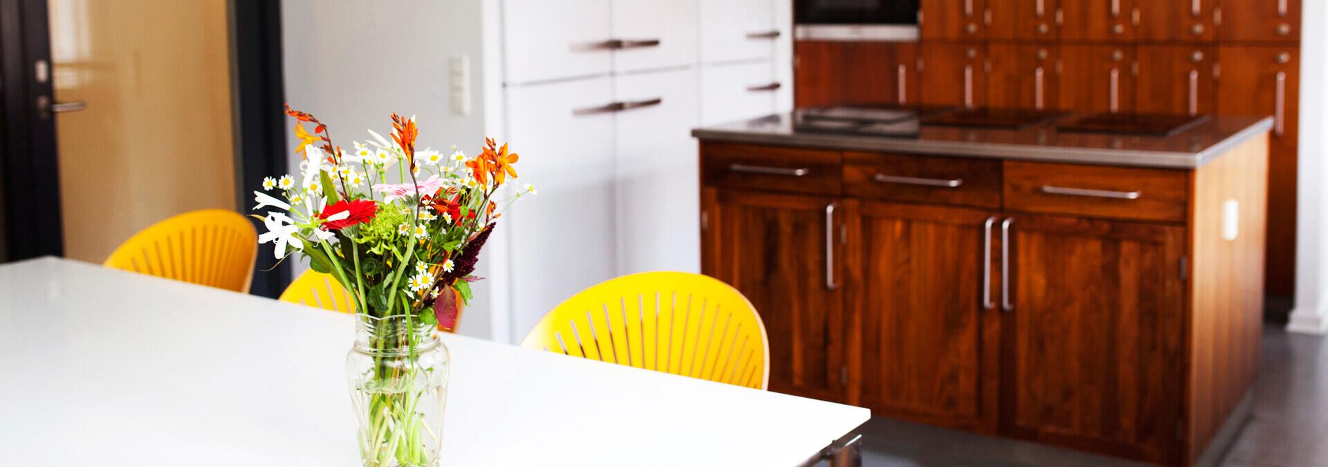 Etagekøkken på krisecenter med borde, stole, komfur, skabe og køleskab
