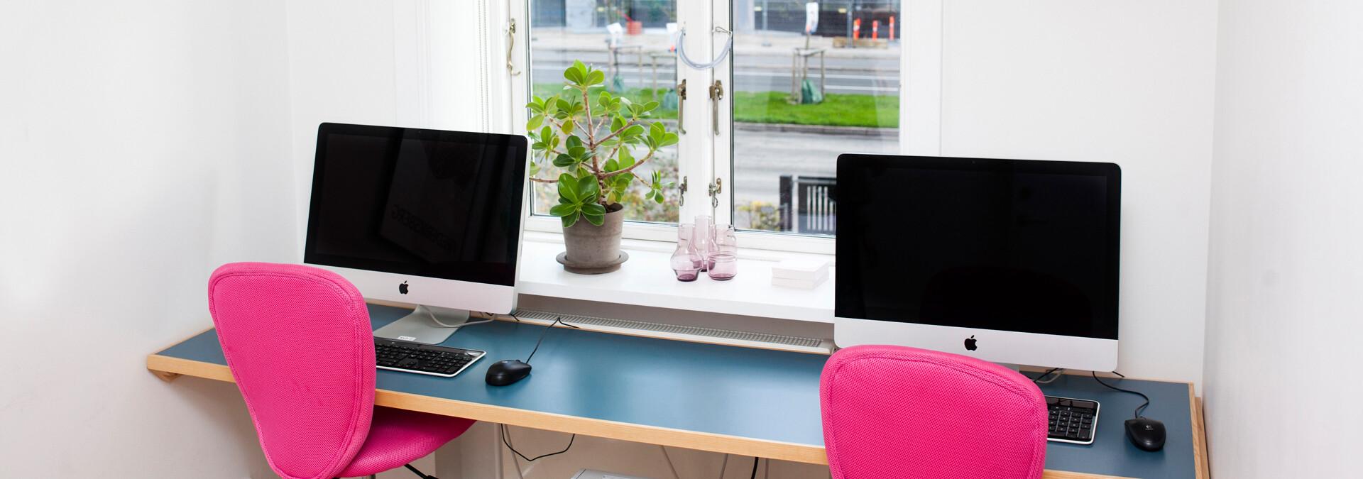Bord med to computere og et vindue på krisecenter