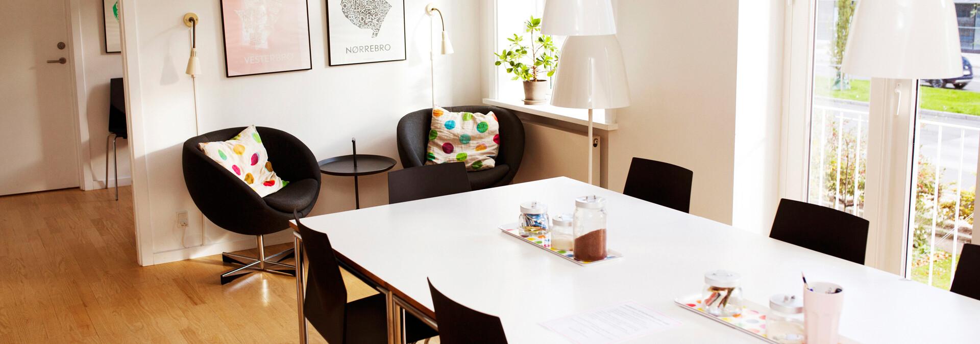 Rum med et stort bord og cafehjørne med puder på krisecenter