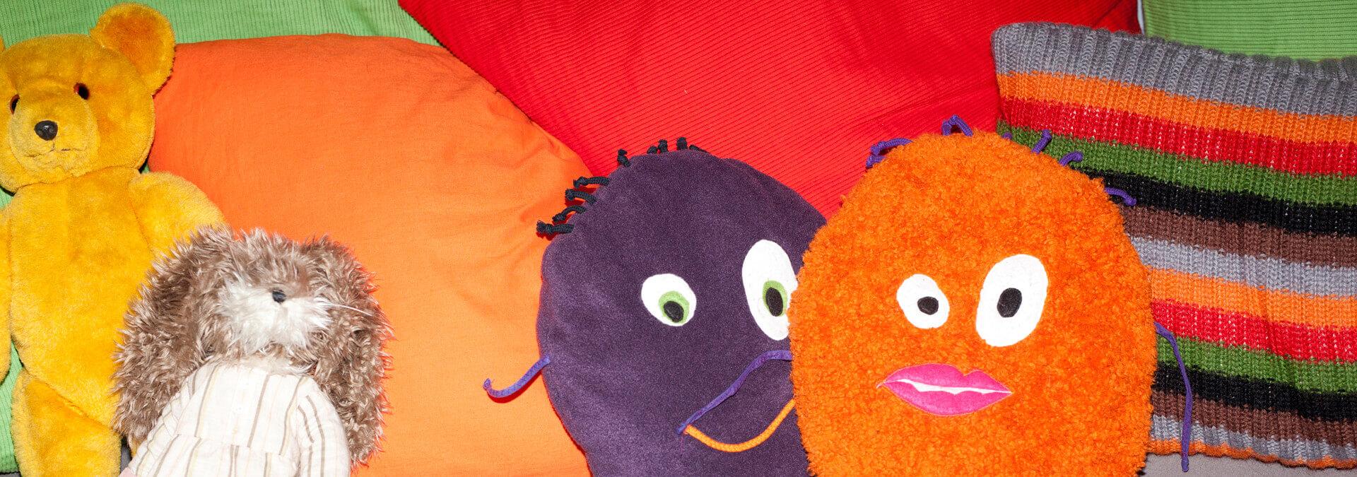 Sofa med puder og to bamser i Børnetræet for børn på krisecenter