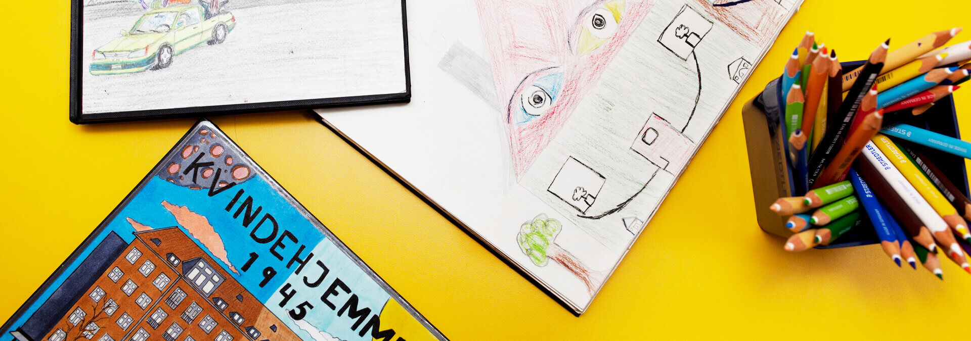 Bøger med tegninger på gult bord med blyanter
