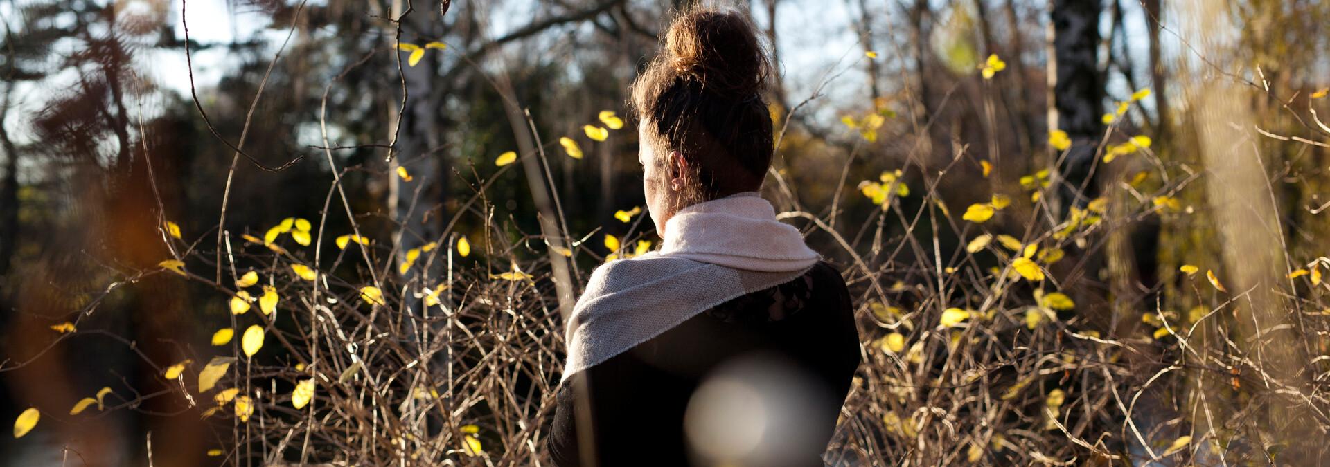 Anonym voldsudsat kvinde på krisecenter ser ud over sø