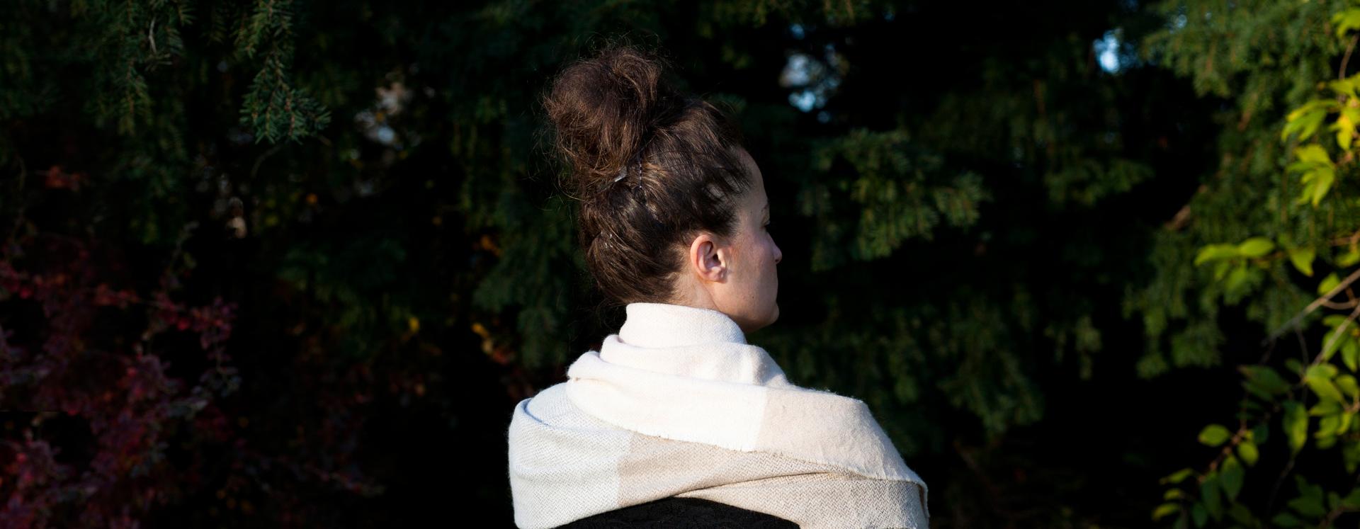 Anonym voldsudsat kvinde på krisecenter står ved nogle buske