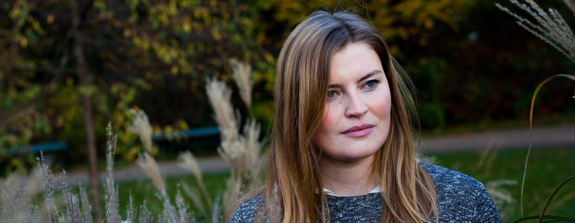 Voldsudsat ung kvinde på krisecenter står i en park med siv bag sig