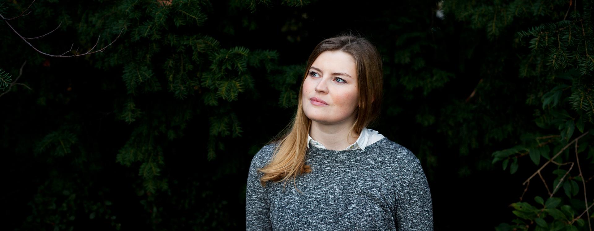 Voldsudsat ung kvinde på krisecenter står ved mørke buske og ser op