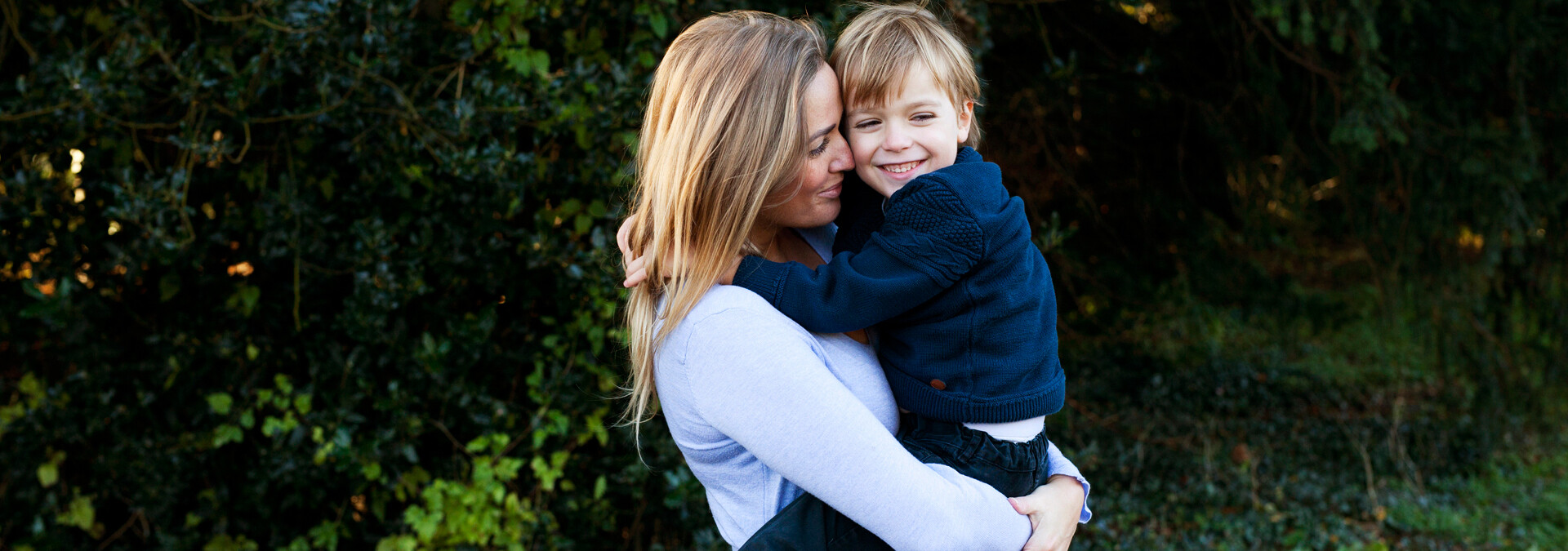 Voldsudsat mor på krisecenter bærer sin søn, som smiler