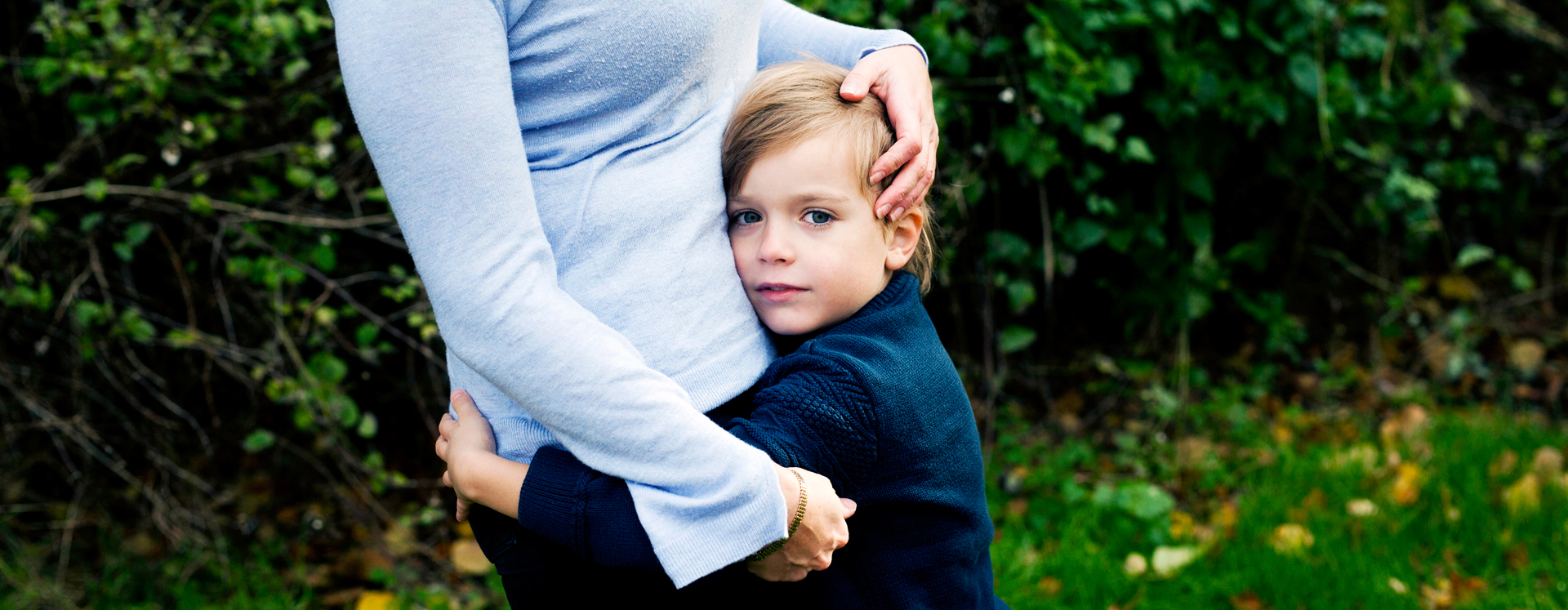 Voldsudsat dreng på krisecenter holder om sin mor i park