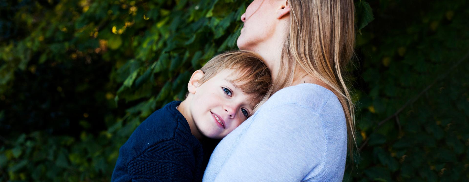 Voldsudsat dreng på krisecenter læner sig op ad sin mors bryst