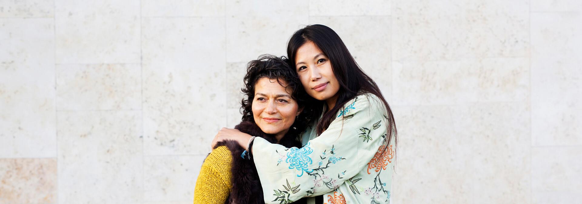 To voldsudsatte kvinder på krisecenter holder om hinanden og smiler
