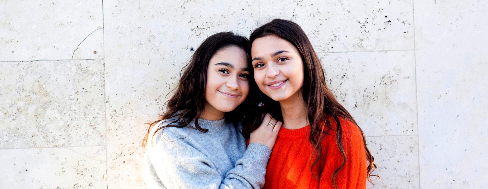 To søskende står tæt sammen og smiler