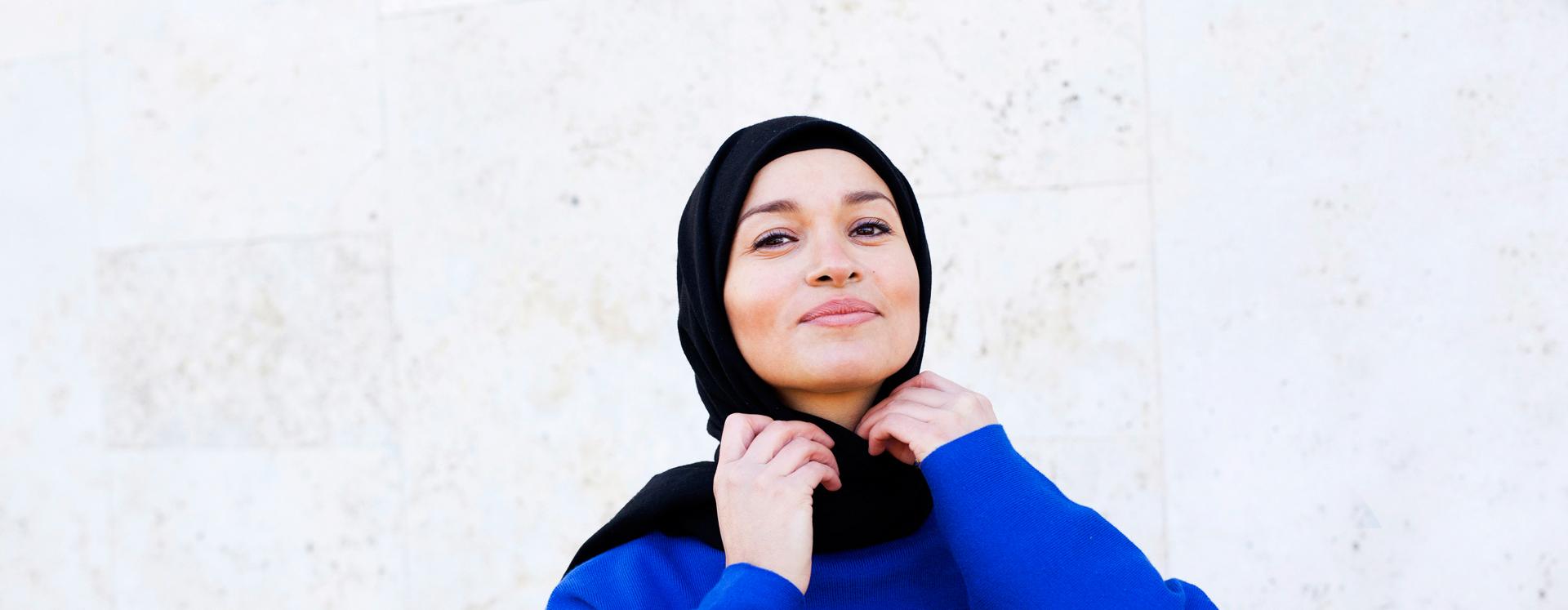 Voldsudsat ung kvinde på krisecenter retter på sit tørklæde mens hun smiler