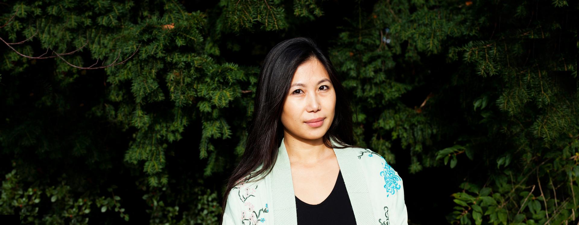 Voldsudsat kvinde på krisecenter står ved buske med solen i ansigtet