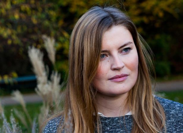 Kvinde udsat for psykisk vold står i en park